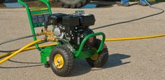 Closeup of a JohnDeere Pressure Washer on a driveway with a tractor in the background