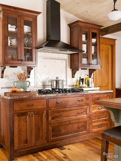 Floors with wood cabs. These inexpensive custom-made alder cabinets combine handmade cabinet boxes with ready-to-assemble face frames, doors, and drawer fronts. Corbels beneath the upper cabinets were crafted out of scraps of alder.