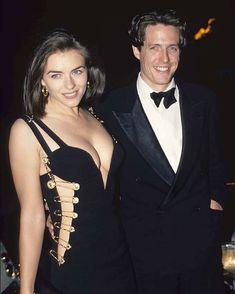 """OBJ Grammy Jewelry Report: Safety Pin Jewelry Rocked by Dua Lipa - Elizabeth Hurley and Hugh Grant at the premiere of """"Four Weddings and a Funeral"""" Gianni Versace - Versace Gold, Gianni Versace, Celebrity Couples, Celebrity Style, Celebrity News, Hugh Grant, Iconic Dresses, Elizabeth Hurley, Celebrity Jewelry"""