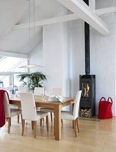 Peisen Austro Flamm har glass på tre sider og er vendbar, slik at flammene kan nytes fra flere vinkler. Eierene kunne ikke benytte seg av det eksisterende pipeløpet, og satte derfor inn nytt røykrør. Dette understreker den store takhøyden og øker ovnens varme-effekt radikalt. Spisebord og stoler er fra tidligere Hilmers hus.