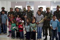 Crianças posam para foto junto à banda.