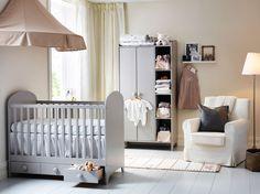 Børneværelse med en lysegrå tremmeseng med skuffer og et garderobeskab. Kombineret med en beige sengehimmel og en hvid lænestol.