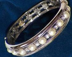 This replica of Jackie Kennedy's wedding bracelet is platinum plated and has 18 faux pearls and 25 Swarovski crystals It was made by Camrose Kross which is best known for its fine jewelry. This bracelet is perfect for work, church or any special occasion. Jackie Kennedy Wedding, Signature Stamp, Wedding Bracelet, Bracelet Box, Thing 1, Swarovski Crystals, Bangles, Pearl Bracelets, Fine Jewelry