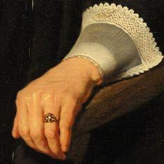 Dettagli 3. Bartholomeus van der Helst: Ritratto di giovane donna. Olio su tela del 1640. Fogg Art Museum, Harvard University. Appoggiata al bracciolo di legno la mano è dettagliata e ben illuminata: si vede la fine della manica nera, nella trasparenza del polsino con il bordo al tombolo.