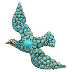 This fine Victorian Turquoise 'Dove' Brooch has been crafted in 14ct yellow Gold in the form of a dove in flight. The impressive brooch is embellished with one hundred and ten cabochon Turquoise of various sizes; the largest Turquoise set to the centre. The eye of the dove is represented with an old mine cut natural Ruby. The dove's head is further embellished with thirteen pavé set Old Dutch cut Diamonds. This brooch secures to the reverse with a hinged pin and security clasp. Circa 1890.