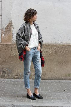 French girl street style // Ivory sweater with plaid scarves layered over the shoulders, cuffed jeans, and simple black loafers