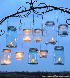 Hanging mason jar tea light holders ...as a collection they make for a unique illuminating work of art ~