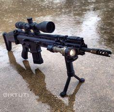SCAR-H. Grip pod. Rail mounted flash light forward. Large scope sight. On wet pavement. jdm
