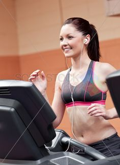 stock photo of smiling athletic woman training on a running machine with earphones in a fitness center