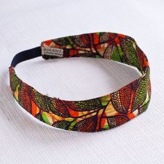 A bright headband handmade from Kitenge, an African garment similar to sarong, often worn by women wrapped around the chest or waist, over the head as a headscarf, or as a baby sling. Handmade by the ladies of the Amani Kenya center. Available in Orange/Green and Yellow/Red.