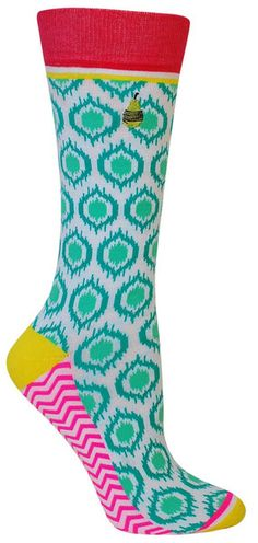 White crew length socks with green and teal shapes, with yellow accents and a white and pink zig-zag bottoms. These socks feature a seamless toe. Fits women's shoe size 5-10.