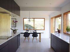 Spisebordet er fra Bolia og Eames-stolene er fra Vitra. Lampen Globe er designet av Verner Panton. Veggen over kjøkkenbenken er dekket med lakkert kryssfiner. Hensikten er å ta inn den organiske følelsen av tre på kjøkkenet.