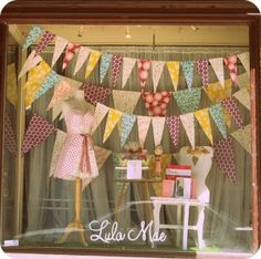 Paper garland gives a playful feel to this window display at Lulu Mae. simple 1 mannequin display with table and chair Spring Window Display, Window Display Retail, Window Display Design, Display Windows, Boutique Window Displays, Fashion Window Display, Merchandising Displays, Store Displays, Retail Displays