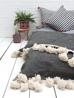 Handwoven cotton rug, blanket or throw with giant wool pom poms in true boho-luxe style.