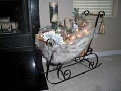 Repurposed faux fur coat, added Birch logs and clear lights,  in a sleigh bought at a consignment shop.   FUN and EASY.