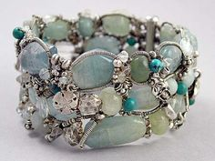 Bracelet constructed with aquamarines of various grades. It also includes turquoise beads, sterling silver shells, animals and beads of various sizes -- all woven up together with silver wire.