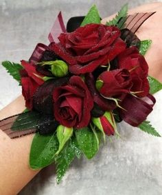 A dramatic prom corsage in red and black featuring spray roses