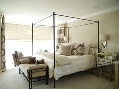 In the master bedroom an iron bed is covered in silk bedding from Ralph Lauren. The sconces are by Suffolk lighting and the mirrored side tables are from Donna Parker.