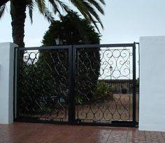 Esta puerta abatible está decorada con esas líneas curvas que le dan un rasgo característico. Cerramientos Candela domina las líneas.