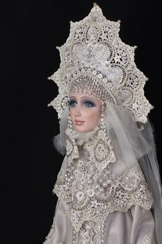 "A porcelain doll in a stylized Russian outfit. The outfit and the headdress ""Kokoshnik"" are made of lace and decorated with artificial pearls."