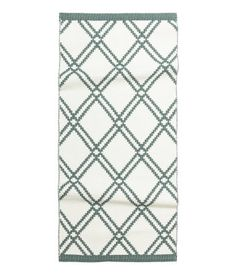 Rectangular cotton rug with a jacquard-weave pattern. Reversible.