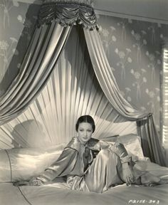 Dorothy Lamour, 1938 bed with fabric ray as headboard and corona with satin hangings