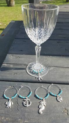 Here are 5 different markers to identify wine glasses. The balls are glass. Wine Glass Markers, Glasses, Markers, Wine Glass, Beach, Vacation, Hands, Eyewear, Eyeglasses