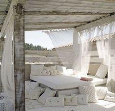 Quel bonheur de pouvoir faire la sieste au sein d'un cadre si agréable ! Sur la terrasse, un lit aménagé avec des coussins et des voilages pour un espace ultra cosy