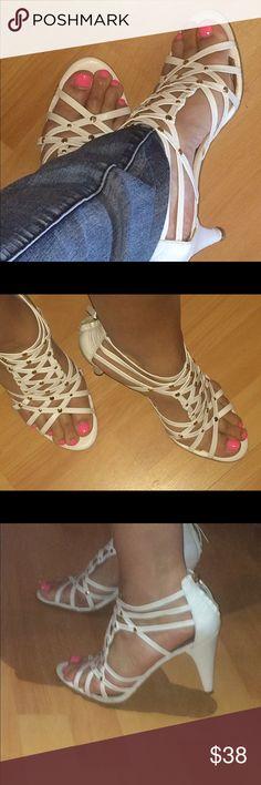Nine West white high heel sandal Nine West white leather high heel sandal. Cross cross straps with gold embellishments. Zipper in back. Super cute with a skirt or your favorite skinny jeans! Nine West Shoes Heels
