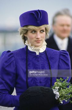 5 March 1986: Prince Charles and Princess Diana visiting Kingston upon Hull, East Yorkshire. Diana wore a purple wool Cossack-style suit by Caroline Charles for Hardy Amies: fitted short jacket that flares over the hips from a nipped-in waist w/ leaf pattern embroidery or applique; full flowing mid-calf-length skirt.  The hat is made of purple velvet.