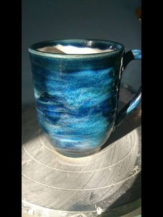 3x storm as base with 3x arctic blue and indigo float stripes. I also applied thick slip whilst the mug was still on the wheel, and dragged my fingers through it up and down whilst the wheel was still turning, to create texture. Artist Emma Millett of Paw Print Pottery