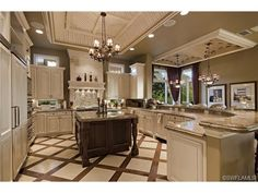 Traditional formal gourmet center island kitchen with wrap around bar - wood inlays in marble floor.  Prato Grand Estates   Talis Park   Naples, FL