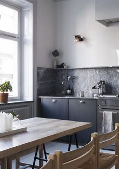 Grey living kitchen - via Coco Lapine Design - love the unusual cabinet design and lovely kitchen table