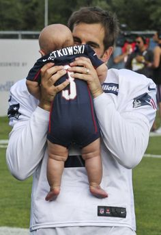 New England Patriots kicker Steve Gostkowski kisses his infant son, Gannon, after practice at NFL football training camp in Foxborough, Mass., Tuesday, July 30, 2013. (AP Photo/Charles Krupa)