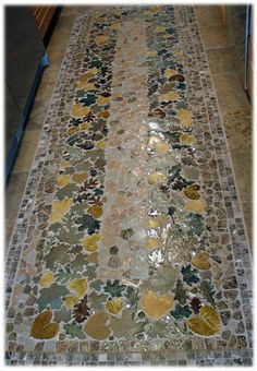 A mix of real stone with ceramic stone shapes and leaf tiles creates a beautiful, rustic rug design.
