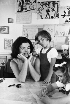 Jackie and Caroline Kennedy watch another student draw a picture at the White House kindergarten.
