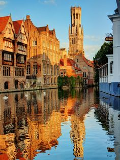 Houses along a canal in Bruges and the Halletoren (the Belfry), Belgium #UNESCO