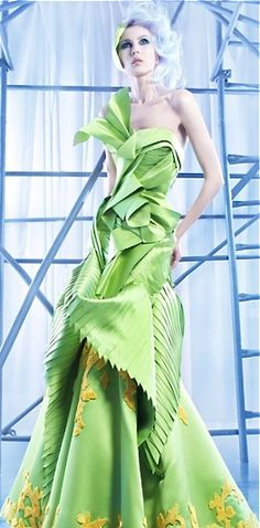 Nicolas Jebran light green gown with pleats, complicated folds and yellow accents.