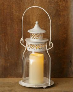 Iron & Glass Lantern with Ivory Pillar Candle. This lantern is equipped with a handle for hanging.