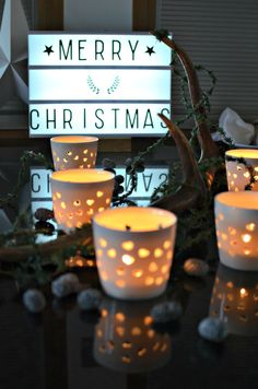Not on the high street : Christmas Decorations : Dining table with a fir garland wrapped around a antler, white ceramic tea lights and fir cones, natural,  simple and elegant.