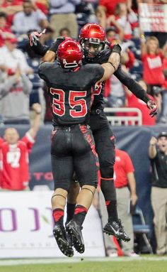 Houston running back Kenneth Farrow, left, celebrates with Xavier Maxwell after Farrow scored a touchdown against South Florida during the first quartern. (James Nielsen/Houston Chronicle/AP)