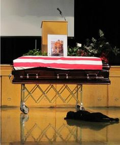 The dog of slain Marine Jon Tumilson refused to leave his side during the Navy SEAL's funeral earlier this week in Rockford, Iowa. The heartbreaking photo taken by his cousin, Lisa Pembleton, shows Tumilson's dog Hawkeye lying by the casket.