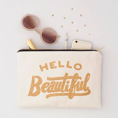 This 'Hello Beautiful' canvas pouch is the perfect complimentary clutch from Alphabet Bags. Printed in super sparkly glitter!Our canvas pouches make fantastic anytime clutch bags and are perfect for carrying your handbag essentials. They also make great makeup bags and are terribly useful when travelling. Makes a great gift for friends, sisters and mothers. The Hello Beautiful design has been screen printed in sparkly gold glitter onto lovely thick canvas with a black cotton lining. The…