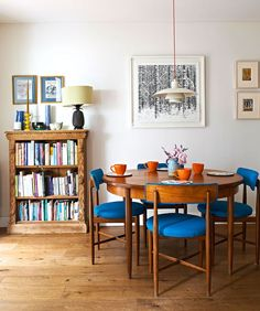Wooden dining table and chairs next to a filled bookcase