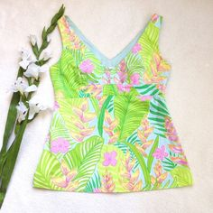 "Lilly Pulitzer Tropical V Neck Sleeveless Top Gorgeous EUC top from Lilly Pulitzer. Bright, tropical pattern with hues of green, pink, light blue and yellow. Sleeveless, V neck, side zip, light blue lining, banded empire waist with a flowy body. Approx flat meas: length 23"", bust 16.5"", band under bust 14.75"", waist 15.5"", hem 20"". Shell 100% cotton, liner 65% polyester, 35% cotton. Machine wash Lilly Pulitzer Tops Blouses"