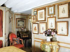 Antique costume drawings hang on the paneled walls of this Parisian apartment library.