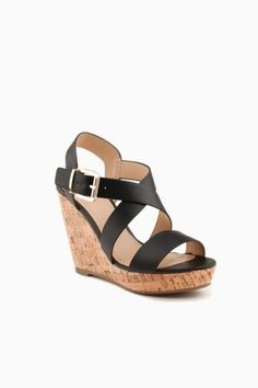Modern meets natural on these wedge sandals, rendered in faux leather and placed on a cork wedge. Buckle closure at ankle cuff.