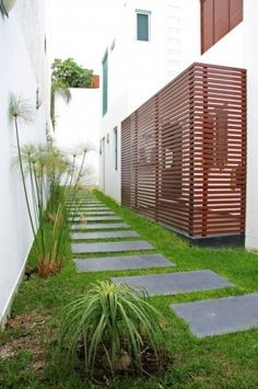 Modern style landscape with dimensional cut stone path and horizontal patterned fencing