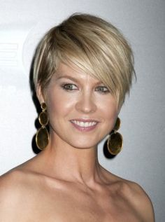 Jenna Elfman's short hair is cut in a cute pixie style, with a lot of razored layers to add texture. Straightened and styled with some pomade completes this piecy looking pixie.