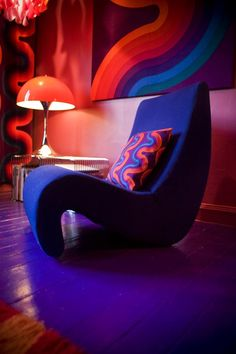 This is beautifully put together with the Panton amoeba chair, patterned scatter cushion, chandelier, lamp and artwork.